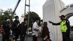 Petugas memeriksa suhu tubuh jemaah yang akan salat Idul Adha 1441 H di Masjid Al-Azhar, Jakarta, Jumat (31/7/2020). Pelaksanaan salat Id dilakukan secara berjemaah di masjid atau lapangan dengan menerapkan protokol kesehatan, seperti mengenakan masker dan menjaga jarak. (Liputan6.com/Johan Tallo)