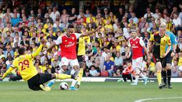 Striker Arsenal, Pierre-Emerick Aubameyang menembakkan bola ke arah gawang ketika pemain Watford, Etienne Capoue  berusaha untuk memblokir tendangannya pada pekan kelima Liga Inggris 2019-2020 di Vicarage Road, Minggu (15/9/2019). Arsenal ditahan imbang 2-2 Watford. (AP/Alastair Grant)