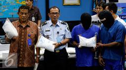 Deputi BNN, Deddy Fauzi El Hakim (kiri) menunjukan barang bukti sabu di Jakarta, Jumat (28/8/2015). BNN berhasil membongkar penyelundupan sabu seberat 103,8 kilogram yang dimasukkan ke dalam mesin sepeda motor dan alat pijat. (Liputan6.com/Yoppy Renato)