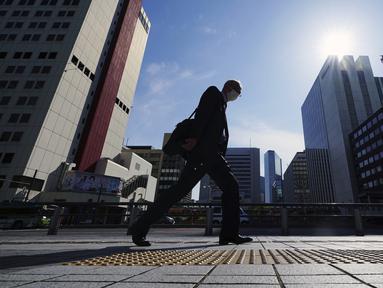Seorang pria yang mengenakan masker pelindung untuk membantu mengekang penyebaran virus corona COVID-19 berjalan di Tokyo, Jepang, Kamis (15/4/2021). Tokyo mengonfirmasi lebih dari 700 kasus baru COVID-19 pada 15 April 2021. (AP Photo/Eugene Hoshiko)