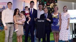 Kiper asal Belgia Thibaut Courtois berpose dengan presiden Real Madrid, Florentino Perez dan kerabatnya selama presentasi dirinya menjadi pemain Real Madrid di stadion Santiago Bernabeu (9/8). (AFP Photo/Javier Soriano)