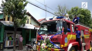 Sepasang pengantin diarak menggunakan mobil pemadam kebakaran setelah selesai melaksanakan ijab qabul. Kejadian unik ini menarik perhatian warga sekitar.