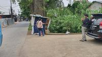 Pemilik warung menunjukan lokasi penemuan bungkusan mencurigakan di warungnya Jalan Raya Grogol, Kecamatan Limo, Kota Depok. Senin (5/4/2021). (Liputan6.com/Dicky Agung Prihanto)