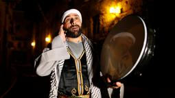 Michel Ayoub, seorang Kristen Arab-Israel, ketika membangunkan kaum muslim untuk melaksanakan sahur di Arce, Israel, Senin (20/6). Michel Ayoub sudah bertahun-tahun membangunkan sahur kaum muslim di sekitarnya selama Ramadan. (REUTERS/Ammar Awad)