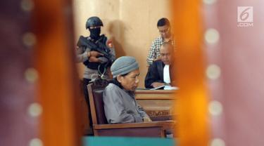 Terdakwa sejumlah kasus tindak pidana terorisme, Aman Abdurrahman saat mengikuti pembacaan tuntutan JPU di PN Jakarta Selatan, Jumat (18/5). Sidang dijaga ketat puluhan personel gabungan bersenjata lengkap. (Liputan6.com/Helmi Fithriansyah)