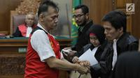Terdakwa kasus penyalagunaan narkoba, Tio Pakusadewo memeluk kuasa hukumnya saat sidang lanjutan di PN Jakarta Selatan, Kamis (12/7). Sidang beragendakan pembacaan duplik atas replik dari JPU pekan lalu. (Liputan6.com/Faizal Fanani)
