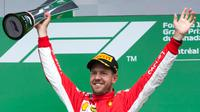 Pembalap Ferrari, Sebastian Vettel mengangkat piala penghargaan usai menjuarai F1 GP di Montreal, Kanada, Minggu (10/6). Vettel menyudahi balapan di posisi terdepan dengan catatan waktu 1 jam 28 menit 31,377 detik. (Ryan Remiorz/The Canadian Press via AP)