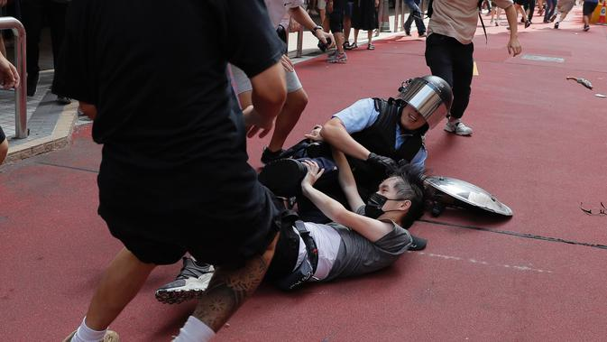 Polisi menahan seorang pria muda setelah perkelahian antara pendukung pro-China dengan demonstran antipemerintah di Amoy Plaza, Distrik Kowloon Bay, Hong Kong, Sabtu (14/9/2019). Beberapa orang ditahan dalam bentrokan ini. (AP Photo/Kin Cheung)