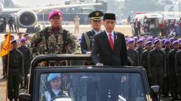 Presiden Joko Widodo menginspeksi pasukan pada perayaan HUT ke-74 TNI di Taxi Way Echo, Lanud Halim Perdanakusuma, Jakarta Timur, Sabtu (5/10/2019). HUT ke-74 TNI diikuti dari seluruh matra. (Liputan6.com/JohanTallo)