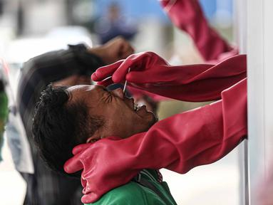 Warga mengikuti tes usap (swab test) COVID-19 di GSI Lab (Genomik Solidaritas Indonesia Laboratorium), Cilandak, Senin (19/10/2020). Pemprov DKI dan DPRD DKI Jakarta berencana mengatur sanksi denda Rp 5juta bagi warga yang menolak rapid test maupun swab test atau tes PCR (Liputan6.com/Faizal Fanani)