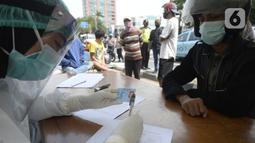 Petugas medis mendata pengendara yang terjaring razia masker di Jalan Panjang, Kedoya, Jakarta Barat, Senin (2812/2020). Pengendara yang tidak mengenakan masker langsung menjalani rapid test antigen gratis untuk mencegah penularan COVID-19. (merdeka.com/Dwi Narwoko)