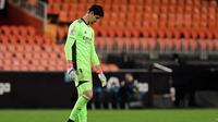 Kiper Real Madrid, Thibaut Courtois tertunduk lesu setelah kalah 1-4 dari Valencia, Senin (9/1/2020). (AFP Photo)