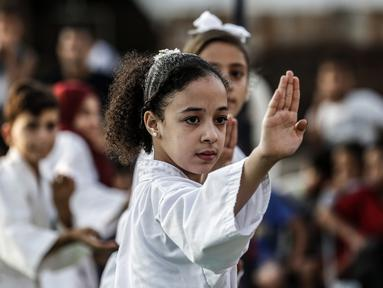 Seorang anak Palestina menunjukkan keterampilannya selama upacara promosi Karate di sebuah pusat olahraga di kamp Rafah untuk pengungsi Palestina di Jalur Gaza selatan (20/9/2019). (AFP Photo/Said Khatib)