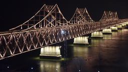 Suasana  Jembatan Persahabatan saat malam terlihat dari kota Dandong di provinsi Liaoning, China (22/2). Pemimpin Korut Kim Jong Un diperkirakan akan melintasi jembatan ini untuk melakukan pertemuan dengan Presiden AS Donald Trump. (AFP Photo/Greg Baker)