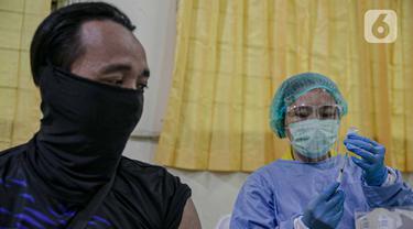 Tenaga kesehatan bersiap menyuntikkan vaksin COVID-19 pada tenaga pendidik di SMP 216, Jakarta Pusat, Selasa (6/4/2021). Pemerintah akan mengatur kembali pemberian vaksin Covid-19 kepada masyarakat karena terbatasnya pasokan vaksin saat ini. (Liputan6.com/Faizal Fanani)