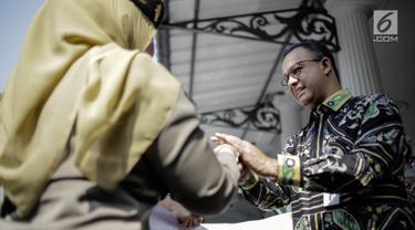Gubernur DKI Jakarta Anies Baswedan bersalaman dengan personel Satpol PP saat pelapasan di halaman Pendopo Balai Kota, Jakarta, Kamis (29/3). (Liputan6.com/Faizal Fanani)