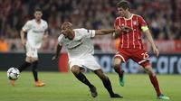 Pemain Sevilla, Steven N'Zonzi (kiri) mencoba melewati adangan pemain Bayern, Thomas Mueller pada leg kedua perempat final Liga Champions di Allianz Arena stadium, Munich, (11/4/2018). Bayern lolos ke semifinal dengan agregat 2-1. (AP/Matthias Schrader)