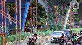 Pengendara melintas dekat dinding Jalan Layang Pesing yang berhias mural di Jakarta Barat, Sabtu (7/12/2019). Mural pada jalan layang sepanjang 1,5 kilometer tersebut merupakan bagian dari program Pemerintah Provinsi DKI Jakarta dalam mempercantik Ibu Kota. (Liputan6.com/Johan Tallo)