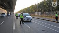Polisi berjaga saat penyekatan di KM 31 Tol Jakarta-Cikampek, Kabupaten Bekasi, Jawa Barat, Sabtu (17/7/2021). Penyekatan ini juga untuk mendukung pemerintah dalam melaksanakan PPKM Darurat guna mencegah penyebaran COVID-19. (Liputan6.com/Herman Zakharia)