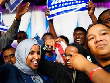 Ilhan Omar bersama pendukungnya merayakan kemenangan putaran pertama pemilihan Distrik Kongres ke-5 di Minneapolis, AS, Selasa (14/8). Omar menjadi muslimah Somalia pertama yang terpilih sebagai anggota Kongres AS. (Mark Vancleave/Star Tribune via AP)