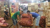 Pedagang membawa buah alpukat di pasar induk Kramat Jati, blok buah di Jakarta, Minggu (2/2/2020). Setidaknya ada lima buah-buahan tropis yang sejatinya diproduksi secara masif di dalam negeri, namun masih diimpor. (Liputan6.com/Herman Zakharia)