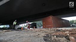 Petugas menutupi tumpahan oli dengan pasir pasca kecelakaan truk kontainer di kolong flyover Tomang, Jakarta, Kamis (28/6). Akibat peristiwa tersebut tumpahan oli tercecer sehingga sebagian jalan terpaksa ditutup sementara. (Merdeka.com/Iqbal S. Nugroho)