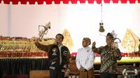 """Presiden Joko Widodo (Jokowi) memainkan wayang kulit disaksikan dalang Ki Mantep Sudarsono (tengah) dalam Pagelaran Wayang Kulit 74 Tahun Indonesia Merdeka di halaman depan Istana Merdeka, Jakarta, Jumat (2/8/2019). Pagelaran wayang mengangkat tema """"Kresno Jumeneng Ratu"""".(Liputan6.com/Angga Yuniar)"""