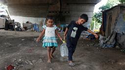 Anak-anak membawa air minum setelah mengisi dari keran kota di bawah jembatan di daerah kumuh di Kalkuta, India (26/5/2016). Kalkuta didirikan Inggris pada 1690 merupakan pusat industri goni dan tekstil. (REUTERS/Rupak De Chowdhuri)