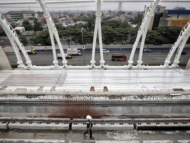 Petugas keamanan melintas di proyek pembangunan Light Rail Transit (LRT) Jabodebek di Stasiun LRT TMII, Jakarta, Senin (14/1). Progres pembangunan Stasiun LRT TMII sudah mencapai 40%. (Liputan6.com/Faizal Fanani)
