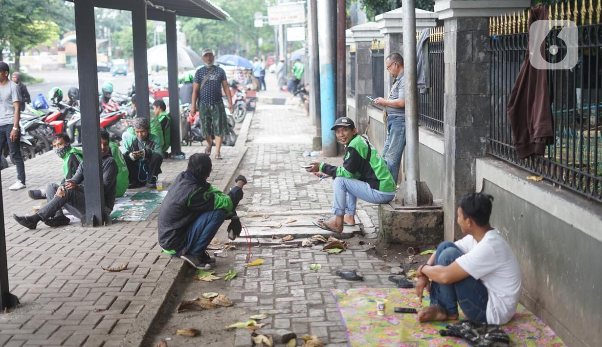 Pengemudi ojek daring menunggu order di depan Cibubur Junction, Jakarta, Selasa (24/3/2020). Merebaknya corona Covid-19 menyebabkan aktivitas di kawasan itu lesu yang juga berimbas pada turunnya pendapatan pengemudi ojol hingga lima kali lipat dibanding hari biasanya (Liputan6.com/Immanuel Antonius)