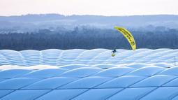 Paraglider Greenpeace terbang ke stadion sebelum pertandingan Grup F Euro 2020 antara Prancis dan Jerman di Allianz Arena, Munich, Jerman, Selasa (15/6/2021). Sang aktivis sempat mengenai peralatan spidercam. (Matthias Balk/DPA via AP)