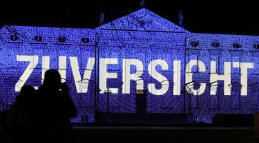 """Pengunjung menikmati pemandangan Istana Bellevue yang diterangi proyeksi cahaya bertuliskan """"Zuversicht"""", yang bermakna keyakinan, di Berlin, ibu kota Jerman, pada 17 Desember 2020. Pertunjukan cahaya bertema """"Lichtblick"""" (Seberkas Harapan) ini digelar di Istana Bellevue di Berlin. (Xinhua/Shan Yuqi"""