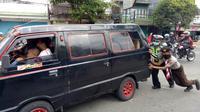 Relawan dan polisi mendorong mobil pemudik yang mogok di Gombong, Kebumen pada arus mudik lebaran 2018, Selasa, 12 Juni 2018. (Liputan6.com/Polres Kebumen/Muhamad Ridlo)