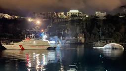 Selebaran foto pada 20 Januari 2021 menunjukkan bangkai paus berukuran besar di pelabuhan Sorrento saat ditarik oleh penjaga pantai Italia menuju pelabuhan Napoli. Bangkai paus itu akan diautopsi oleh ahli biologi kelautan dan ahli lain yang mencari penyebab kematiannya. (HO/GUARDIA COSTIERA/AFP)