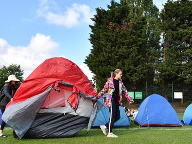 Dua wanita memindahkan tenda mereka ketika mengantre untuk membeli tiket pada hari pertama turnamen tenis Kejuaraan Wimbledon 2019 di The All England Tennis Club di Wimbledon, London barat daya (1/7/2019). Turnamen ini dimulai 1 Juli-14 Juli 2019. (AFP Photo/Ben Stansall)