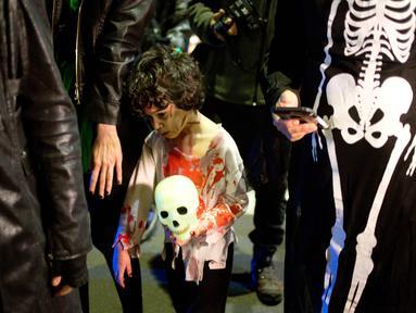 Seorang bocah mengenakan kostum zombie saat mengikuti Zombie Walk dalam Festival Purim di Tel Aviv, Israel (3/3). Purim merupakan hari raya atau pesta Yahudi untuk memperingati pembebasan kaum Yahudi dari kekaisaran Persia. (AP Photo/Ariel Schalit)