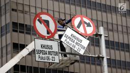 Petugas Dishub mencabut rambu larangan melintas untuk sepeda motor di Jalan MH Thamrin, Jakarta Pusat, Rabu (10/1). MA membatalkan Pergub DKI soal pelarangan sepeda motor melintasi Jalan MH Thamrin hingga Medan Merdeka Barat. (Liputan6.com/Arya Manggala)