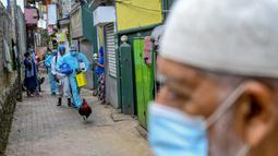 Petugas kesehatan tentara berjalan melalui gang saat melakukan vaksinasi virus corona COVID-19 untuk penduduk sebuah wilayah di Kolombo, Sri Lanka, Kamis (12/8/2021). (Ishara S. KODIKARA/AFP)