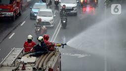 Petugas pemadam kebakaran (Damkar) melakukan penyemprotan cairan disinfektan di sepanjang jalan Thamrin-Sudirman, Jakarta, Sabtu (28/3/2020). Penyemprotan menggunakan mobil pemadam kebakaran tersebut bertujuan untuk mengantisipasi penyebaran Virus Corona (COVID-19). (merdeka.com/Imam Buhori)