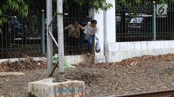 Warga menerobos pagar untuk menyeberangi rel kereta api di kawasan Lenteng Agung, Jakarta, Selasa (19/3). Tidak adanya JPO menyebabkan warga harus menerobos pagar besi, meskipun perilaku tersebut berbahaya bagi keselamatan.(Liputan6.com/Immanuel Antonius)