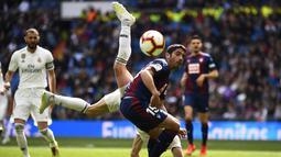 Striker Real Madrid, Gareth Bale, berebut bola dengan bek Eibar, Jose Angel, pada laga La Liga di Stadion Santiago Bernabeu, Sabtu (6/4). Real Madrid menang 2-1 atas Eibar. (AFP/Gabriel Bouys)