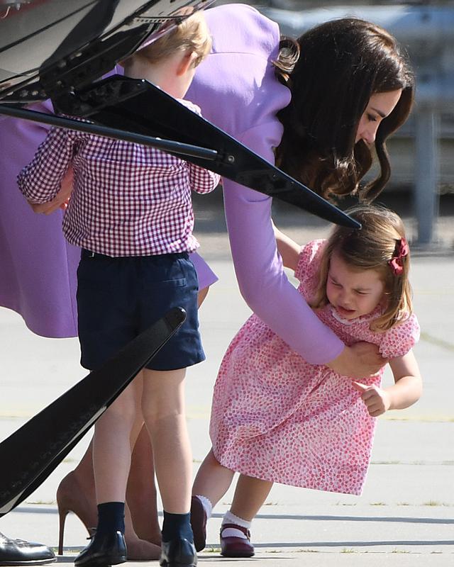 Kate Middleton berusaha menggendong anaknya, Putri Charlotte, yang merajuk dalam kunjungan mereka ke Pabrik Airbus di Hamburg, 21 Juli 2017. Putri Charlotte mendadak merajuk dan enggan naik helikopter di pabrik pesawat terbang itu. (Patrik STOLLARZ / AFP)