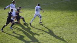 Striker Leeds United, Patrick Bamford, berebut bola dengan pemain Burnley, James Tarkowski, pada laga Liga Inggris di Stadion Elland Road, Minggu (27/12/2020). Leeds United menang dengan skor 1-0. (Laurence Griffiths/Pool via AP)