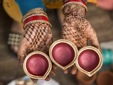 Seorang wanita India menunjukkan lampu dari tanah liat untuk menyambut Diwali, festival cahaya bagi umat Hindu, di New Delhi, India (8/11/2020). Umat Hindu di seluruh penjuru India menghias rumah mereka dengan lampu dari tanah liat dan menyalakan lilin untuk merayakan Diwali. (Xinhua/Javed Dar)