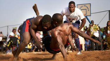 Seorang pegulat menjatuhkan lawannya dalam festival gulat tradisional di Bamako, Mali, 7 April 2019. festival gulati ini digelar setiap tahun di Bamako. (MICHELE CATTANI/AFP)