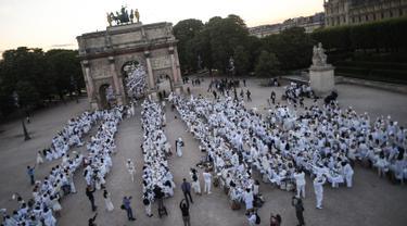 """Para peserta dalam balutan serba putih  berkumpul untuk Dinner en Blanc atau """"makan malam putih"""" di Tuileries Gardens, Paris, Kamis (6/6/2019). Gelaran yang berlangsung sejak 1988 ini dilengkapi dengan meja makan yang dihiasi taplak, kursi dan peralatan makan bernuansa putih. (Lucas BARIOULET/AFP)"""