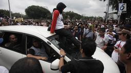 Demonstran berusaha mencegat driver online yang masih beroperasi saat unjuk rasa di depan Istana Negara, Jakarta, Rabu (14/2). Aksi pemberhentian mobil taksi online itu membuat situasi tegang antar pengemudi dan demonstran. (Liputan6.com/Arya Manggala)