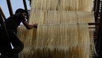 Pekerja India menggantung helai bihun untuk dikeringkan di sebuah pabrik di Ahmadabad pada 16 Mei 2019. Bihun sangat diminati di kalangan muslim India karena merupakan menu favorit yang kerap disuguhkan saat berbuka puasa bersama dengan buah-buahan manis. (AP Photo/Ajit Solanki)