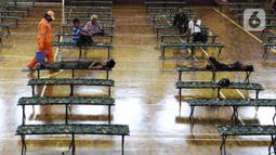 Petugas PPSU usai membersihkan lantai GOR Ciracas, Jakarta, Selasa (28/4/2020). Untuk mencegah meluasnya penyebaran virus Covid-19, Pemprov DKI Jakarta menyiapkan seluruh GOR di Jakarta untuk menampung sementara tunawisma. (Liputan6.com/Helmi Fithriansyah)