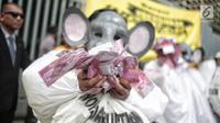 Massa yang tergabung dalam koalisi #BersihkanIndonesia menggelar aksi teatrikal di depan Gedung Bawaslu, Jakarta, Selasa (15/1). Massa aksi terdiri dari aktivis Greenpeace, Auriga, JATAM dan ICW. (Liputan6.com/Faizal Fanani)
